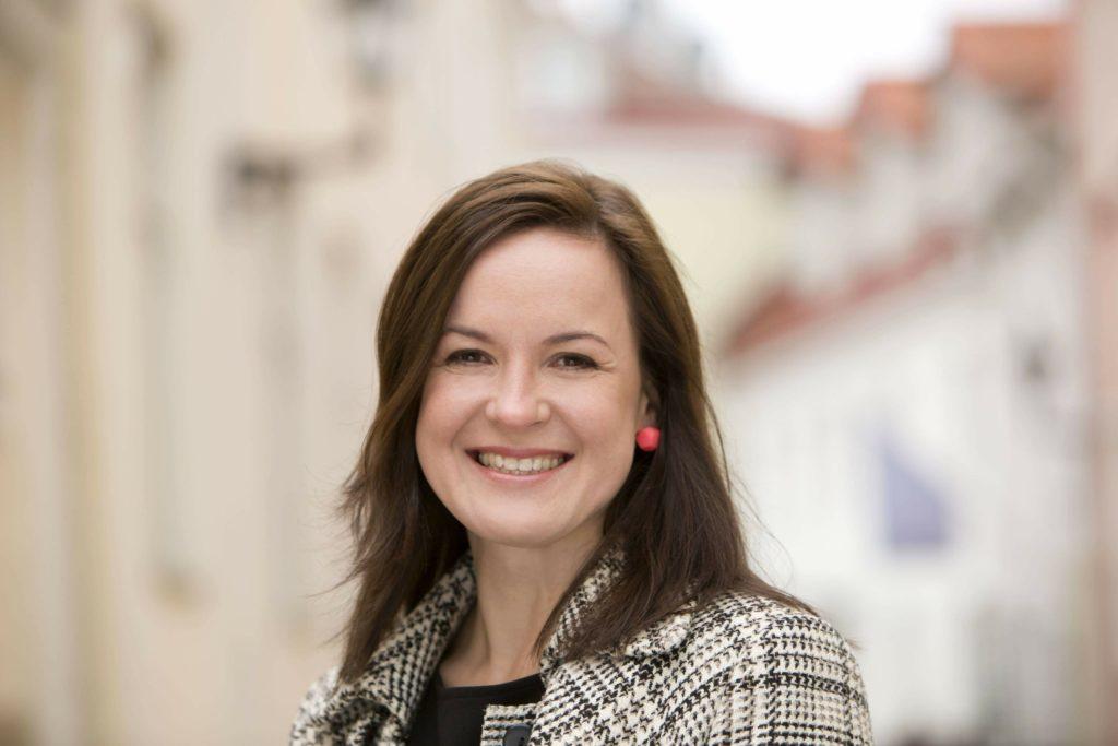 Ruskeatukkainen nainen hymylee kuvan keskellä, taustalla Tallinna
