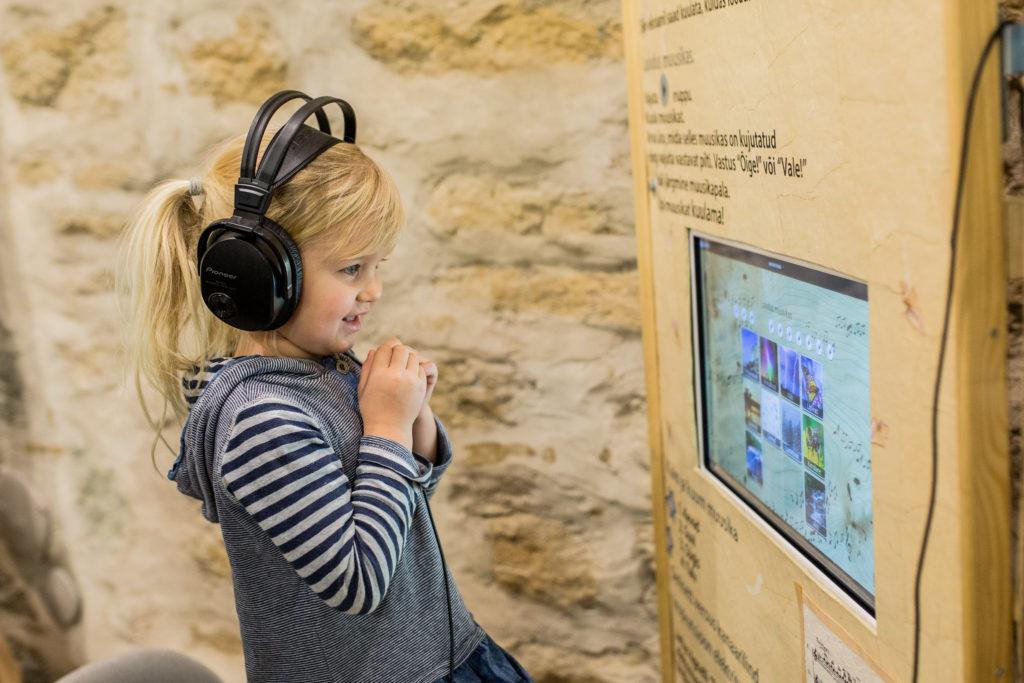 Tyttö Narvan museossa kuulokkeet päässä ja näyttöpäätteen edessä. Kuva: Aron Urb/ Visit Estonia.