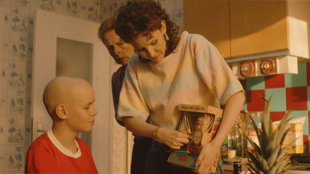 Kohtaus elokuvasta: nainen painaa Gorbatshov-nuken ääninappia ja poika kuuntelee.