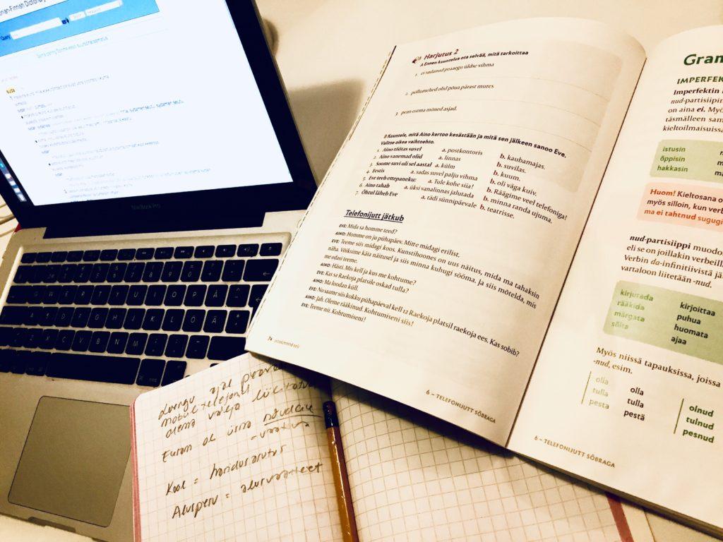 Pöydällä tietokone, vironkielen oppikirja ja vihko, jossa merkintöjä