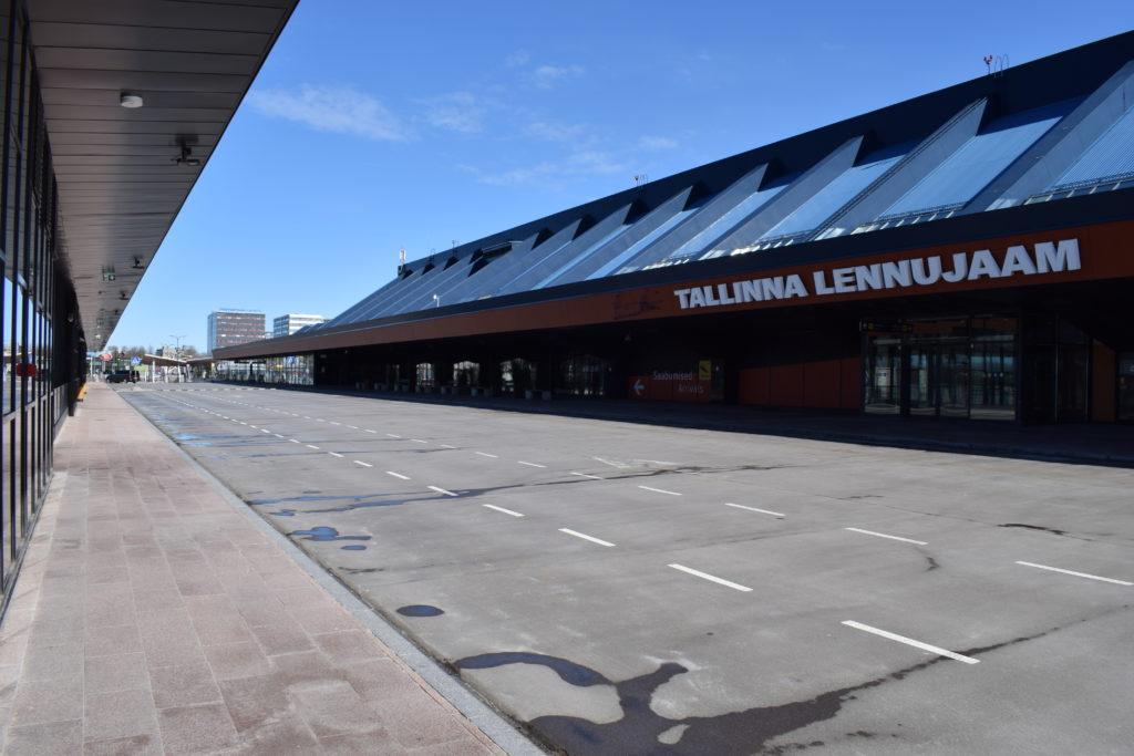 Pitkä ja kapea rakennus, sisääntuloaula lentokentälle. Katon harjassa lukee: Tallinna Lennujaam, eli Tallinnan lentokenttä.
