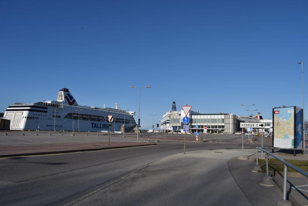 Vasemmalla iso risteilylaiva ja edessä toinen. Tie on tyhjillään keskellä, ei autoja eikä ihmisiä missään.