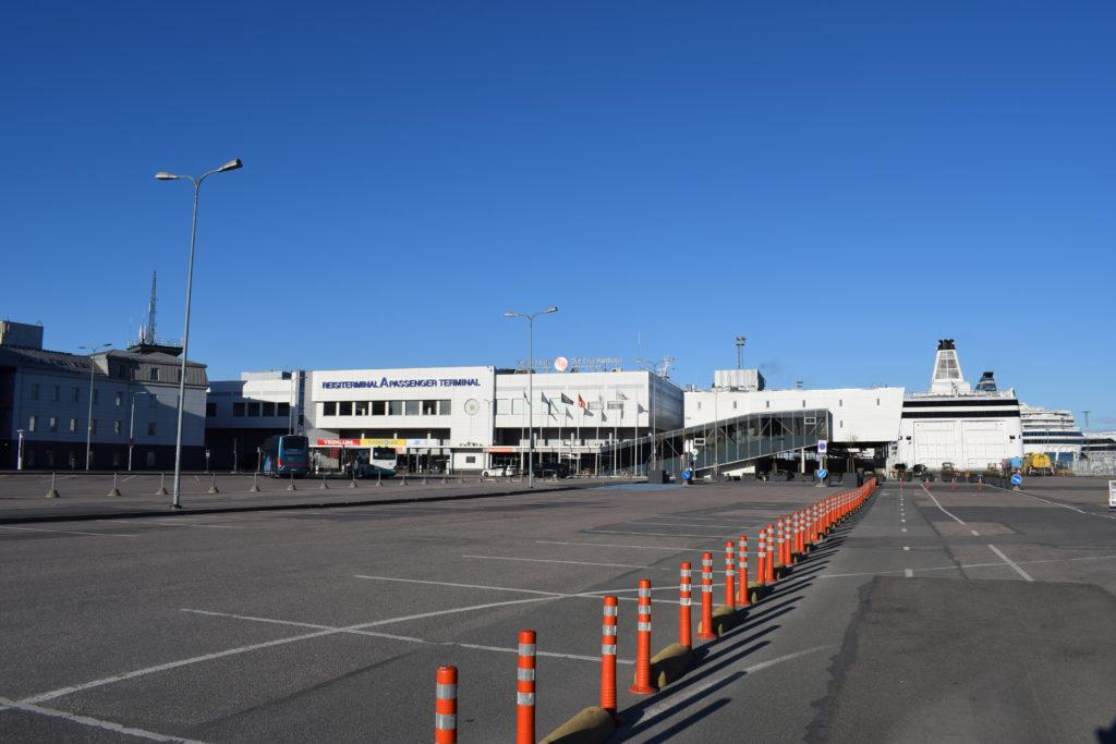 A-Terminal Tallinnassa, keskellä tyhjä parkkipaikka ja horisontissa siintää valkoisia rakennuksia. Keskellä kuvaa punaisia liikennekartioita.