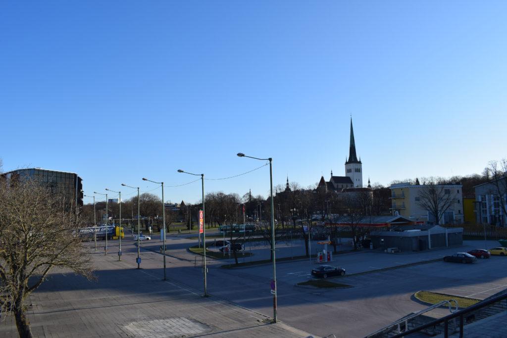 Taustalla siintää kirkon torni. Edessä tyhjiä parkkipaikkoja.