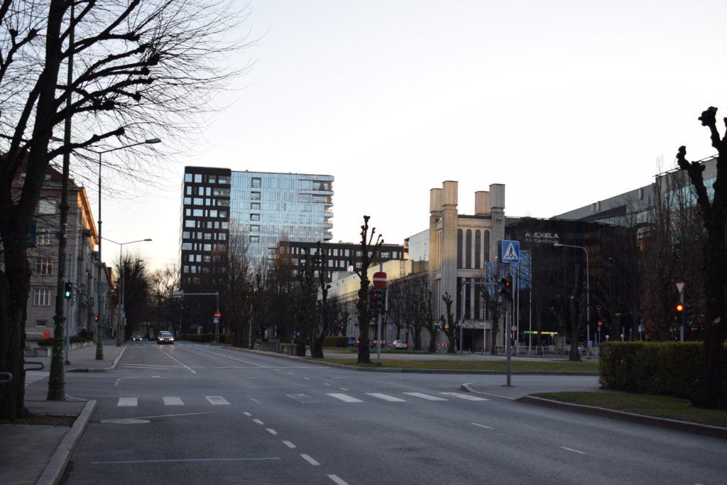 Edessä kaupunkimaisemaa: lasinen kerrostalo, historiallisen näköinen matalampi rakennus. Tyhjät tiet, ilta-aurinko paistaa.