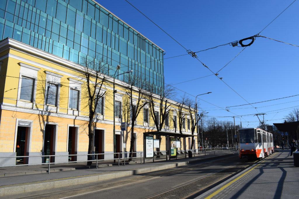 Keskekllä tyhjä katu ja tyhjä ratikkalaituri, johon saapuu juuri ratikka. Vasemmalla keltainen rakennus ja lasirakennus. Aurinko paistaa, kadut ovat tyhjät.