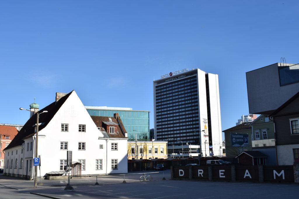 Vasemmalla valkoinen matala tiilitalo, johon aurinko paistaa kirkkaasti. Horisontissa Viru-hotelli ja muita rakennuksia. Oikealla edessä kirjaimet D R E A M kiinnitetty aitaan.
