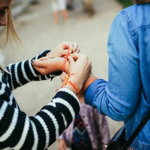 Kaksi ihmistä kuvassa, kuvan laidoilla. Tyttö raitapaidassa sitoo toisen henkilön kateen punottua nauhaa.