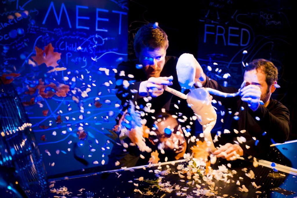 Kuva teatteriesityksestä. Kolme miestä tekee nukketeatteria valkoisen nuken kanssa, nuken päälle sataa konfetteja ja lehtiä.