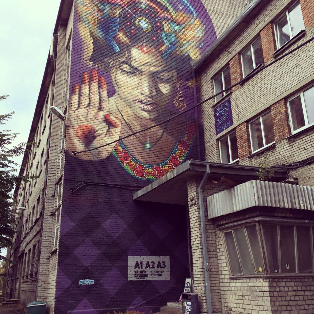 Graffititaidetta Tallinnassa. Iso teos seinässä, nainen, jonka silmit kiinni ja käsi pystyssä, mystinen tunnelma.