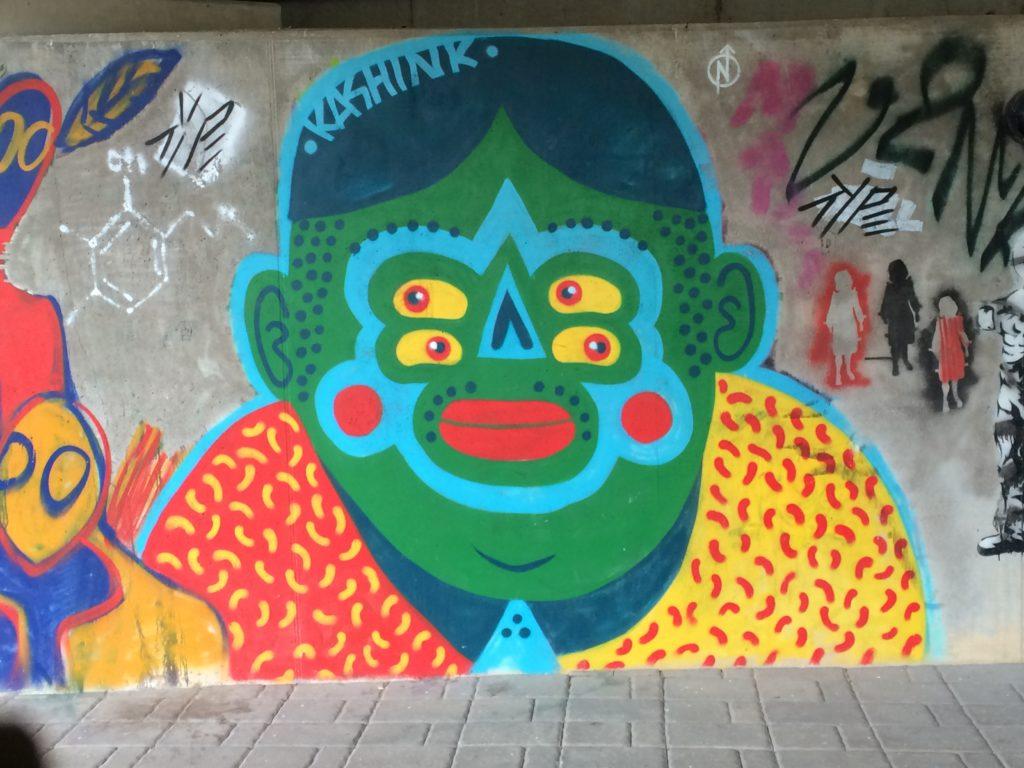 Graffititaidetta Tartossa. Iso värikäs monisilmäinen olento.