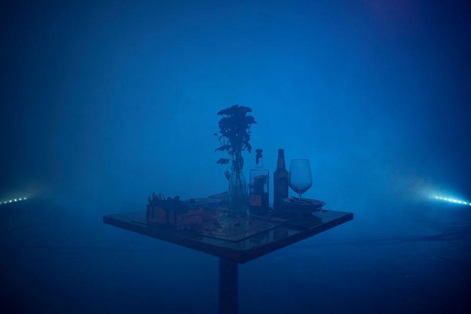 Kuva teatteriesityksen lavastuksesta. Sininen savu taustalla ja keskellä kuvaa pöytä, jossa erilaisia jouimiseen ja syömiseen liittyviä asioita, myös vaasissa oleva kukka.