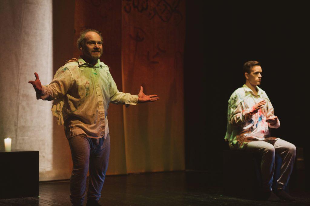 Kuva teatteriesityksestä: yksi mies istuu kuvan oikeassa reunassa, toinen seisoo kuvan vasemmassa reunassa. Kummallakin päällä vaalea paita, joka on sotkettu eri väreillä.