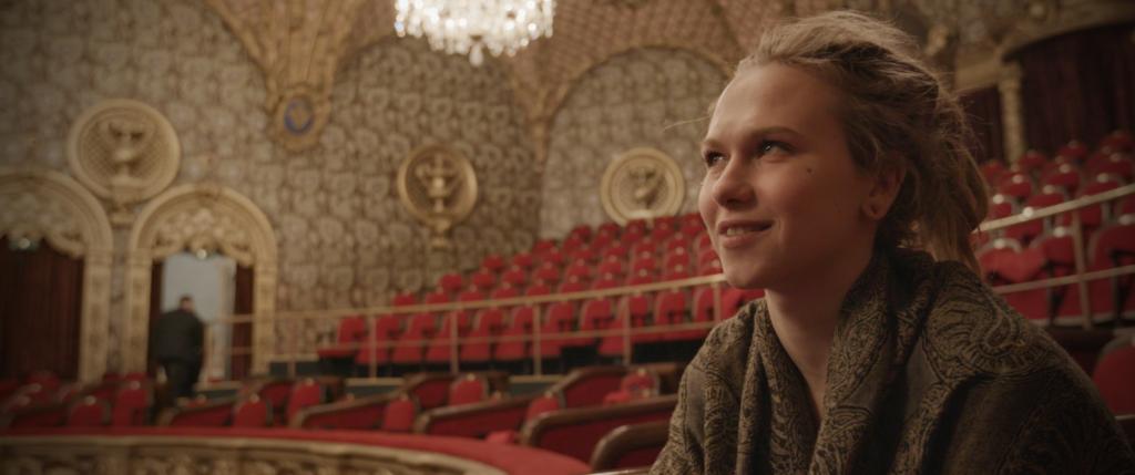 Teatterisali, joka on tyhjillään muuten, paitsi elokuvan päähenkilö istuu ja hymyilee.