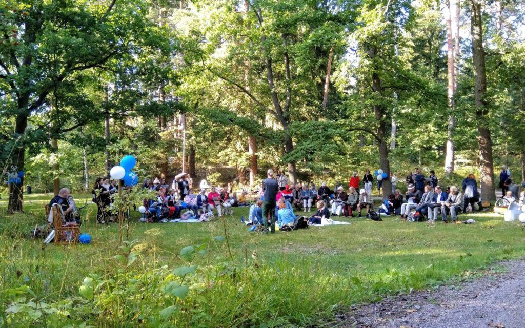 Puistonäkymä, jossa istuu ihmisiä vilteillä, laulamassa yhdessä.