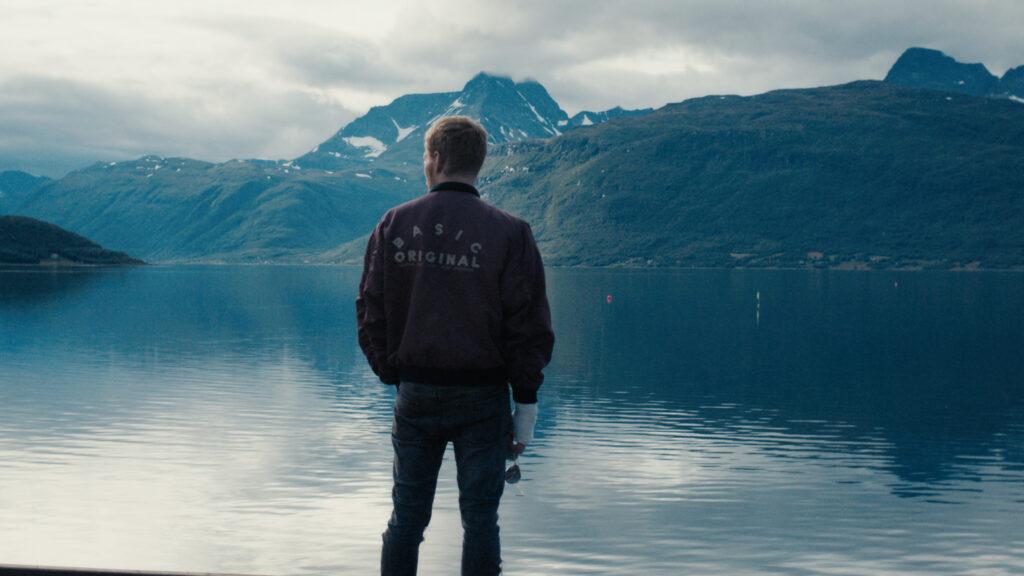 Mies seisoo selkä kuvajaan päin, katsoen jylhää lappilaismaisemaa, jossa meri ja vuoria etäällä.