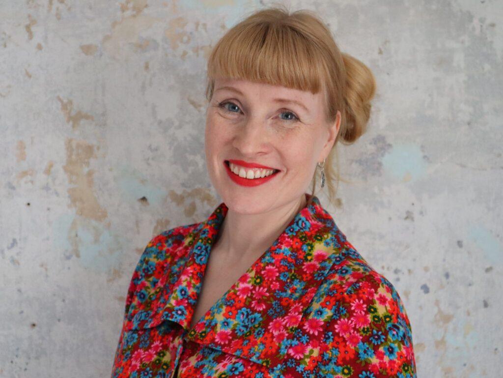 Heidi Iivari kuvattuna rinnasta ylöspäin, päällään punainen mekko ja taustalla vaalea kiviseinä.