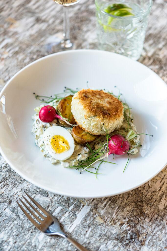 Valkoinen lautanen, jossa kalapiirakka, salaattia ja kananmuna.